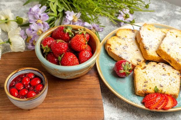 Vorderansicht leckere kuchenstücke mit erdbeeren auf süßem kuchenkuchen der hellen oberfläche