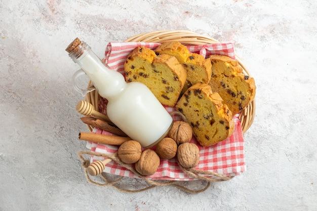 Vorderansicht leckere kuchenstücke mit milch und walnüssen auf hellweißer oberfläche