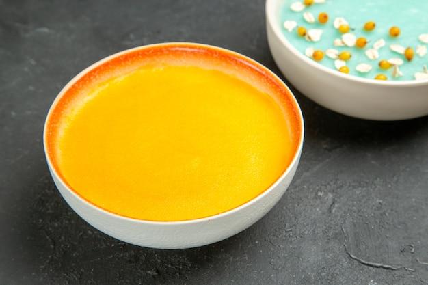 Vorderansicht leckere kürbissuppe innerhalb platte auf dunkler tischschale farbsuppe