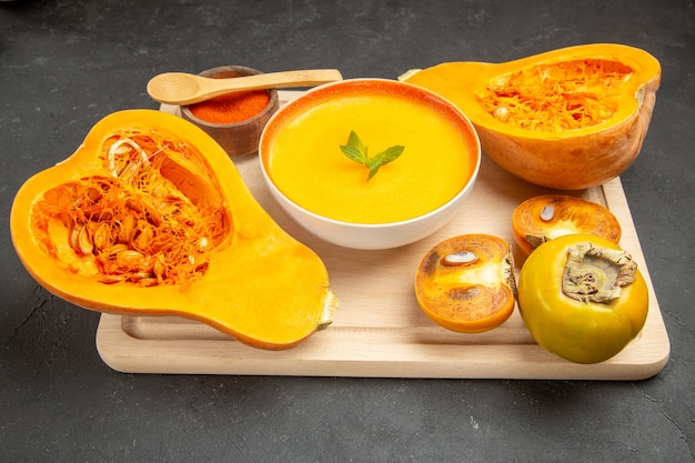 Vorderansicht leckere kürbissuppe mit frischen kürbissen auf der leichten schreibtischschale fruchtsuppe