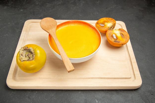 Vorderansicht leckere kürbissuppe mit kakis auf dunkler tischschalenfarbsuppe