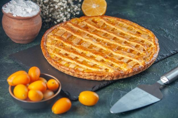 Vorderansicht leckere kumquats-torte auf dunkelblauem hintergrund