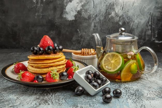 Vorderansicht leckere pfannkuchen mit frischen früchten auf süßem obstkuchen der leichten oberfläche