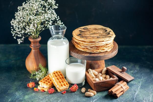 Vorderansicht leckere pfannkuchen mit frischer milch und nüssen auf dunkelblauem dessertkuchen honigkuchen frühstück süßer milchmorgen