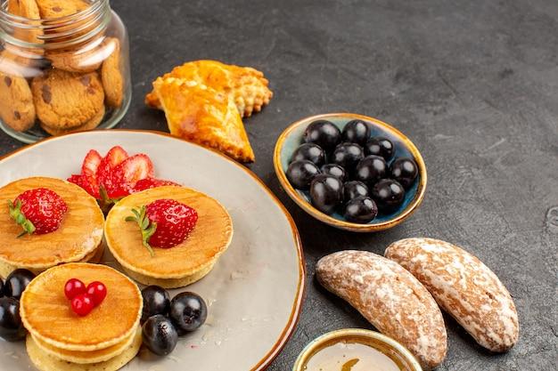 Vorderansicht leckere pfannkuchen mit früchten und kuchen auf dunklem obstkuchen der dunklen oberfläche