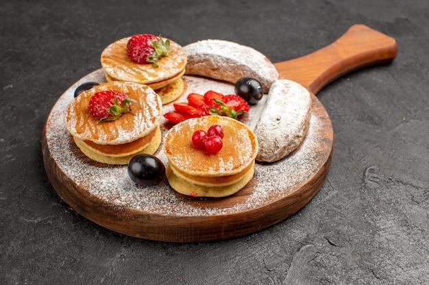 Vorderansicht leckere pfannkuchen mit früchten und kuchen auf dunkler oberfläche süße kuchenfrucht