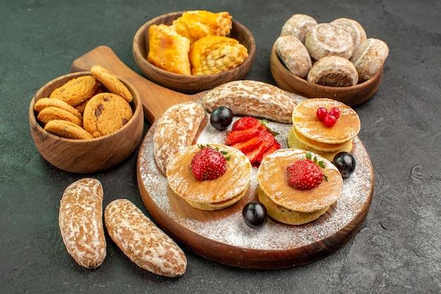 Vorderansicht leckere pfannkuchen mit früchten und süßen kuchen auf der dunklen oberfläche süßer kuchen nachtisch