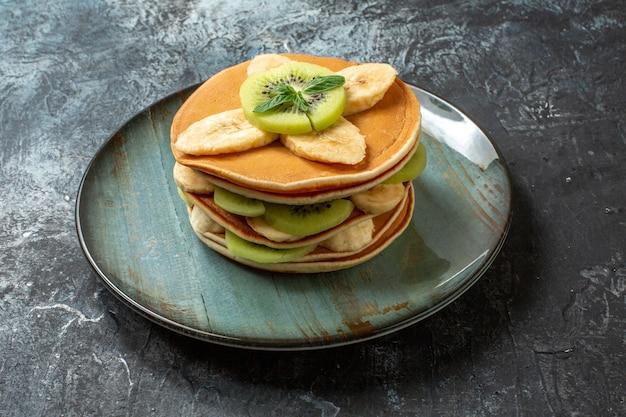 Vorderansicht leckere pfannkuchen mit geschnittenen kiwis und bananen auf dunkler oberfläche fruchtdessert frühstückskuchen zuckerfarbe süß