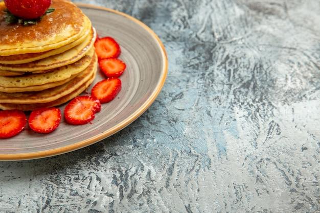Vorderansicht leckere pfannkuchen mit honig und erdbeeren auf der leichten oberfläche kuchenfrucht süß