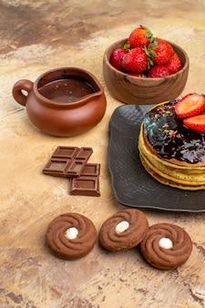 Vorderansicht leckere pfannkuchen mit keksen und früchten auf einem hölzernen schreibtischdessertkuchen süßer kuchen