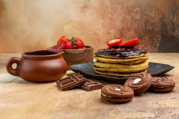 Vorderansicht leckere pfannkuchen mit keksen und früchten auf holzschreibtisch