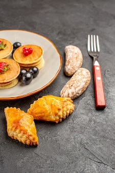 Vorderansicht leckere pfannkuchen mit kuchen und früchten auf dunklem obstkuchen der dunklen oberfläche