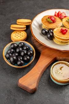 Vorderansicht leckere pfannkuchen mit oliven und früchten auf dunklem obstkuchen der dunklen oberfläche