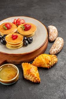 Vorderansicht leckere pfannkuchen mit oliven und kuchen auf dunkler oberfläche früchte süßer kuchen