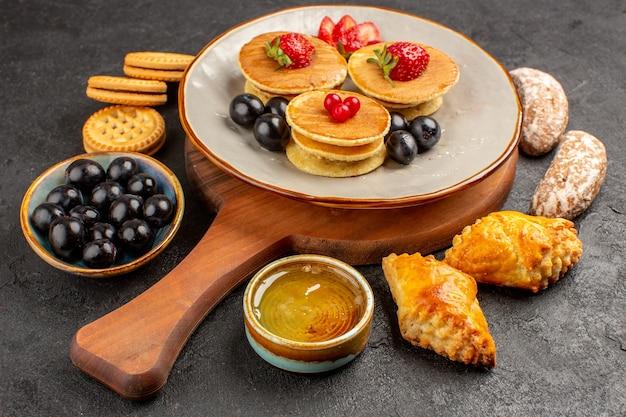 Vorderansicht leckere pfannkuchen mit oliven und kuchen auf süßem obstkuchen der dunklen oberfläche