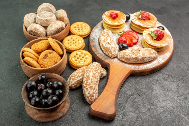 Vorderansicht leckere pfannkuchen mit süßen kuchen und früchten auf der dunklen oberfläche süßer kuchen dessert
