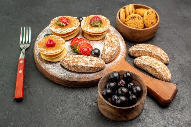 Vorderansicht leckere pfannkuchen mit süßen kuchen und früchten auf dunkler oberfläche kuchen dessert süß