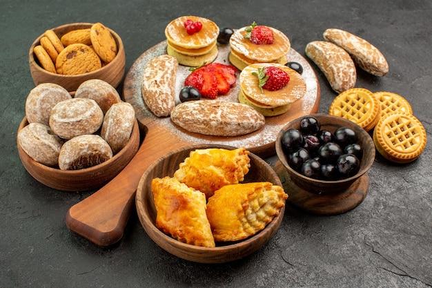 Vorderansicht leckere pfannkuchen mit verschiedenen süßigkeiten auf dunklem oberflächenzuckerkuchen-dessert