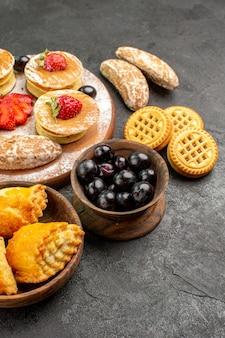 Vorderansicht leckere pfannkuchen mit verschiedenen süßigkeiten auf dunkler oberfläche kuchen zuckerdessert