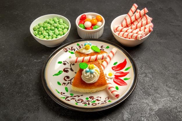 Vorderansicht leckere sahnetorte im gestalteten teller mit süßigkeiten auf dunklem raum