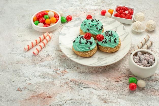 Vorderansicht leckere sahnetorten mit bunten bonbons auf weißem hintergrund kuchen keks süße dessertcreme