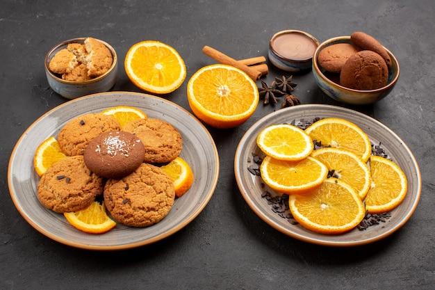 Vorderansicht leckere sandkekse mit frisch geschnittenen orangen auf dunklem hintergrund obstkeks süßer keks zucker zitrusfarbe