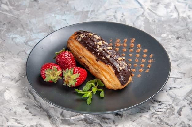 Vorderansicht leckere schoko-eclairs mit erdbeeren auf dem leuchttisch dessert kuchen süßigkeiten