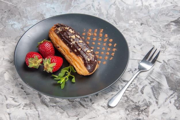 Vorderansicht leckere schoko-eclairs mit erdbeeren auf hellem tischkuchen-dessert-bonbon