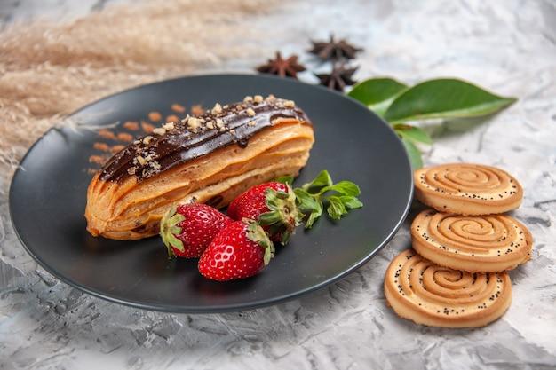 Vorderansicht leckere schoko-eclairs mit keksen auf leuchttisch-keks-kuchen-dessert-keks