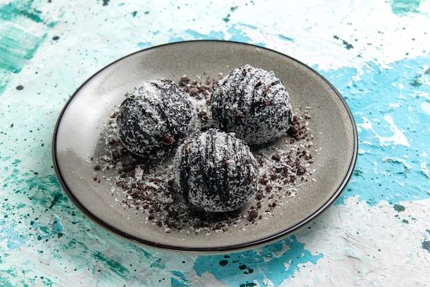 Vorderansicht leckere schokoladenbällchen schokoladenkuchen rund geformt mit zuckerguss auf der blauen oberfläche kuchen backen keks süße zuckerschokolade