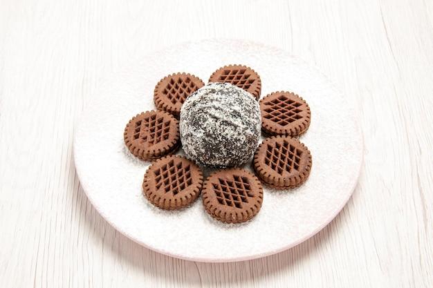 Vorderansicht leckere schokoladenkekse mit kleinem kakaokuchen auf weißem schreibtisch schokoladenkuchen-kuchen-keks-keks-tee