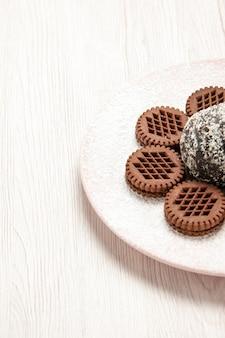 Vorderansicht leckere schokoladenkekse mit kleinem kakaokuchen auf weißem schreibtisch schokoladenkuchen kuchen kekse keks tee