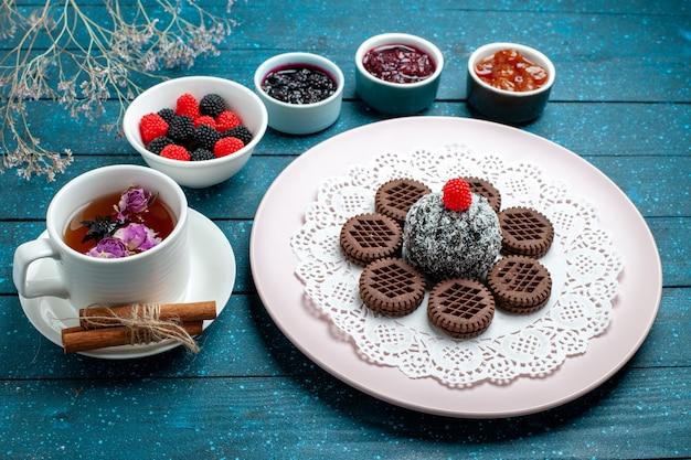 Vorderansicht leckere schokoladenkekse mit marmelade und tasse tee auf blauem rustikalem schreibtischkuchen kakaotee süßer kekskeks