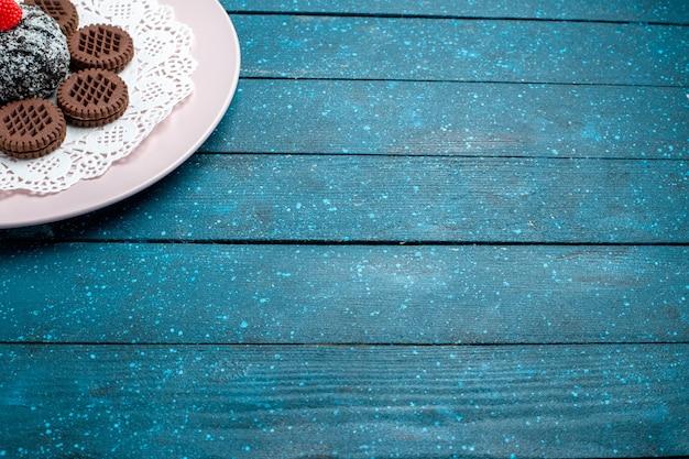 Vorderansicht leckere schokoladenkekse mit schokoladenkuchen auf blauem schreibtischkuchen kakaotee süßer keksplätzchen