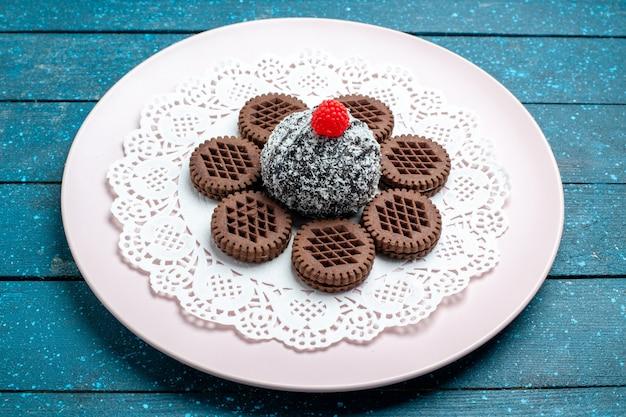 Vorderansicht leckere schokoladenkekse mit schokoladenkuchen auf dem blauen rustikalen schreibtischkuchen kakaotee süßer keksplätzchen