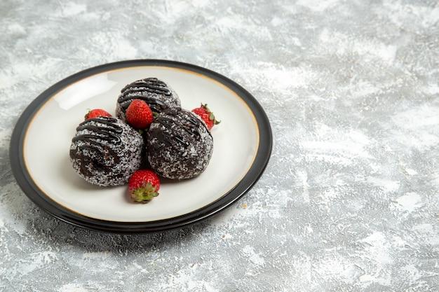 Vorderansicht leckere schokoladenkuchen mit erdbeeren auf der weißen oberfläche backen kekszuckerkuchen süße keksschokolade