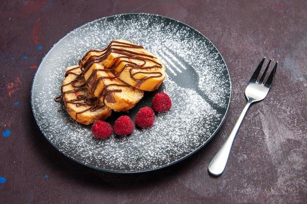 Vorderansicht leckere süße brötchen geschnittener kuchen für tee im teller auf dem dunklen raum dark