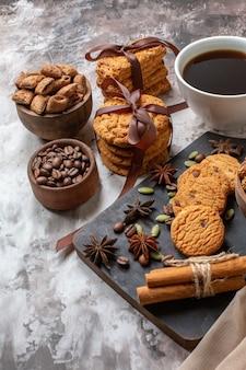 Vorderansicht leckere süße kekse mit kaffeesamen und tasse kaffee auf heller hintergrundfarbe kakaozuckerteeplätzchen süßer kuchenkuchen