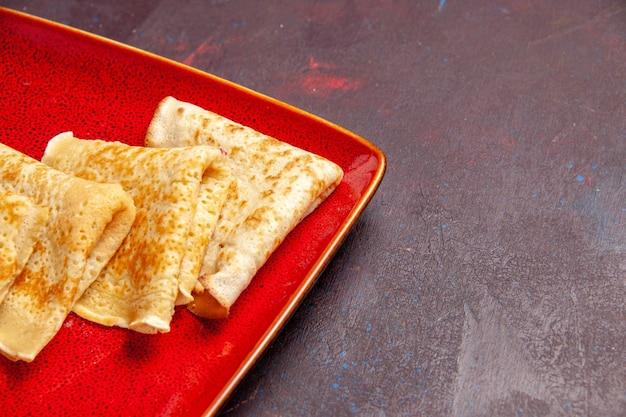 Vorderansicht, leckere süße pfannkuchen in der roten platte auf dunklem raum