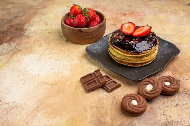 Vorderansicht leckere süße pfannkuchen mit keksen auf holzschreibtisch dessertkuchen süße torte