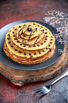 Vorderansicht leckere süße pfannkuchen mit schokoladenglasur auf einem dunklen hintergrund