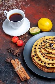 Vorderansicht leckere süße pfannkuchen mit tasse tee auf einem dunklen hintergrund süße kuchenmilchdessert