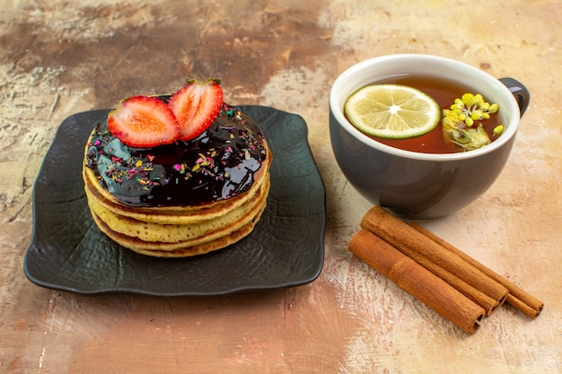 Vorderansicht leckere süße pfannkuchen mit tasse tee auf leichter schreibtischkuchen süße dessertmilch