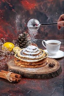 Vorderansicht leckere süße pfannkuchen mit zuckerpulver auf dunklem hintergrund