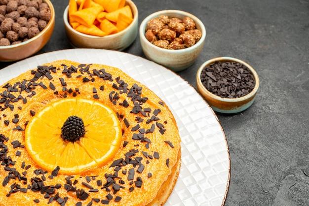 Vorderansicht leckere süße torte mit orangenscheiben auf grauem schreibtisch tortenkeks dessert süßer kuchentee