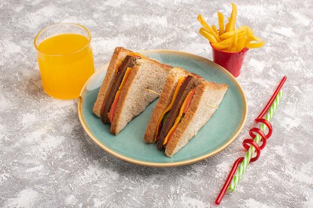 Vorderansicht leckere toastsandwiches mit käseschinken innerhalb der blauen platte mit pommes fritesaft auf weiß