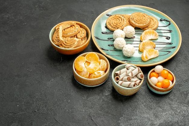 Vorderansicht leckere zuckerkekse mit bonbons auf dunkelgrauem tischkeksplätzchenkuchen