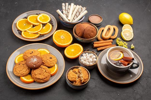 Vorderansicht leckere zuckerkekse mit tasse tee und orangen auf dunklem hintergrund zuckertee-fruchtkeksplätzchen süß