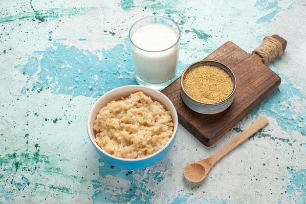 Vorderansicht leckeren brei mit milch auf dem blauen schreibtisch frühstück mahlzeit mahlzeit milch