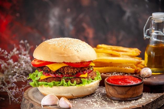 Vorderansicht leckeren fleischburger mit pommes frites auf dunklem boden